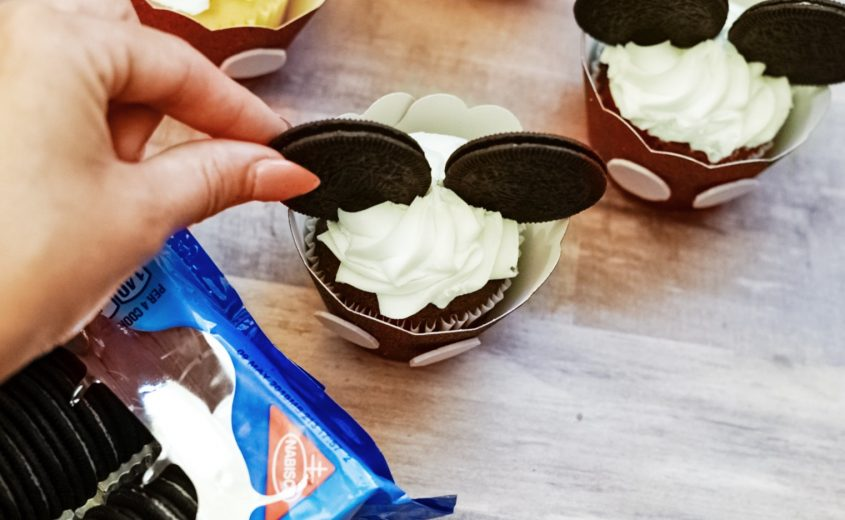 Step 3: Glue two Mickey buttons onto each cupcake wrap.