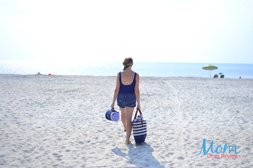 woman walking on beach with towel and bag
